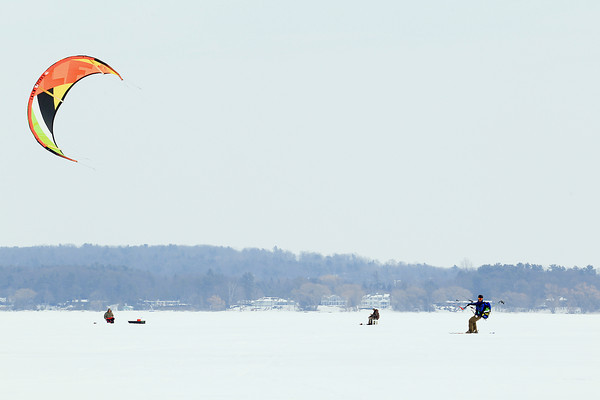 Record-Eagle/Keith King<br /> John Fahey, of Traverse City, snowkites past ice fishermen Friday on West Grand Traverse Bay as he and others snowkite toward the end of Old Mission Peninsula. Fahey is a head coach with the Broneah Kiteboarding company.