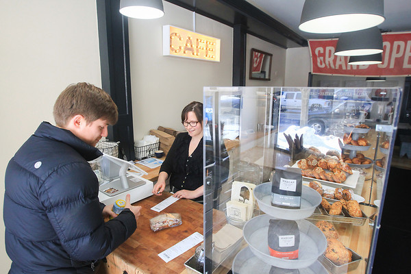 Record-Eagle/Keith King<br /> Michael Kent, left, of Traverse City, makes a purchase from Vanessa Clark, manager, at Pleasanton Cafe on Union Street in downtown Traverse City.