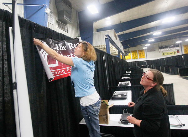 "Record-Eagle/Keith King<br /> Lisa Parks, left, with The Reverse Mortgage Center, sets up her exhibit area as Rachel Krino, with Bailey Designs and Consulting, and media coordinator for the ""Ideas for Life"" Senior Expo, assists as preparations are made for the expo scheduled for Wednesday in Howe Arena at the Grand Traverse County Civic Center."