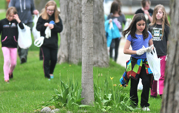Record-Eagle/Nathan Payne<br /> Central Grade School third-grader Olivia Phillips looks for trash along the streets near the school Phillips and 79 other members of the school's Girls on the Run group spent Tuesday afternoon picking up trash in the neighborhood as part of the club's community service. The girls will join hundreds more from other area school Saturday to run a 5k race after the Bayshore Marathon.