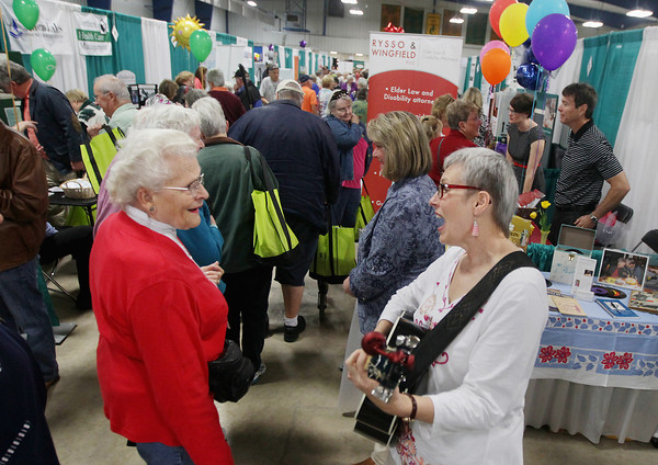 Record-Eagle/Keith King<br /> Ellen Weber, left, of Old Mission Peninsula, and a member of the Grand Traverse Show Chorus of Sweet Adelines, sings and dances while listening to Mary Sue Wilkinson, owner of Young at Heart Music, sing and play guitar Wednesday, May 15, 2013 during the Ideas for Life Senior Expo, presented by Bay Area Senior Advocates, in Howe Arena at the Grand Traverse County Civic Center. Profits from the event are to be administered by the Grand Traverse County Commission on Aging for area seniors in need.