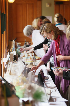 Record-Eagle/Keith King<br /> Janis Adams, of Traverse City, looks at an item Saturday, May 11, 2013 as attendees gather and mingle near items placed on tables for a silent auction during the Power of the Purse event at the City Opera House to benefit women and families staying at the Goodwill Inn.