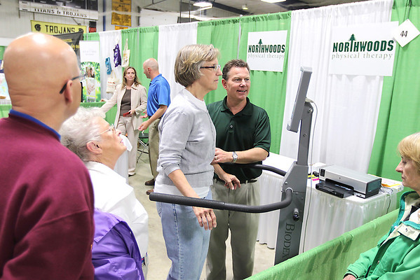 """Record-Eagle/Keith King<br /> David Rapson, board certified physical therapist and owner of Northwoods Physical Therapy, talks with Joyce Tkach as she stands on a machine that assesses an individual's balance Wednesday, May 18, 2011 during the 10th annual Ideas for Life Senior Expo at the Grand Traverse County Civic Center. The event was sponsored by the Bay Area Senior Advocates (BASA). """"It's nice having everything in one spot and getting information,"""" Tkach said."""