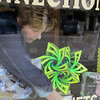 Record-Eagle/Keith King<br /> Roxanne Lutey, owner of The Nature Connection, places information in her store window Tuesday near an art piece created by ninth-grade Northport student  Monnie Raphael as a part of Green Elk Rapids Days' Trashformations recycled creations competition.