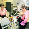 Record-Eagle/Keith King<br /> Tammy Lynch, right, of Traverse City, holds Delainey Deering while being helped by Sarah Montgomery, co-owner of Wishbones, on Thursday inside Cedar Creek Interiors in Traverse City. The cafe is scheduled to be open from 7:00 a.m. to 3:00 p.m. Monday through Saturday.