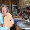 Record-Eagle/Glenn Puit<br /> Carol Winkler holds one of the cutting boards she makes in the garage of her Benzie County home. Winkler is seeing increased demand for the boards made from cherrywood. The board she is holding was freshly cut. She stains and cures the boards before sale.