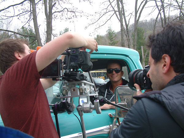 Record-Eagle/Marta Hepler Drahos<br /> Country musician Matt Austin smiles from behind the wheel of a 1965 Ford pickup truck as filmmaker Sam Logan Khaleghi and cinematographer Carl Ballou capture the action for a music video.