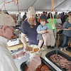 """Record-Eagle/Keith King<br /> Volunteer Fred Marsh Jr., left, of Grawn, serves food to Nels Veliquette, of Traverse City, holding his son Axel Veliquette, 2, as his wife, Michelle Veliquette, right, stands nearby Sunday, May 19, 2013, during Northwestern Michigan College's 58th annual barbecue. """"It's our favorite community event, every year we don't miss it,"""" Michelle said."""