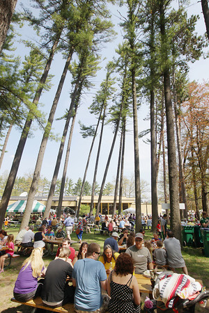 Record-Eagle/Keith King<br /> Attendees enjoy food under the pine trees Sunday, May 19, 2013, during Northwestern Michigan College's 58th annual barbecue.