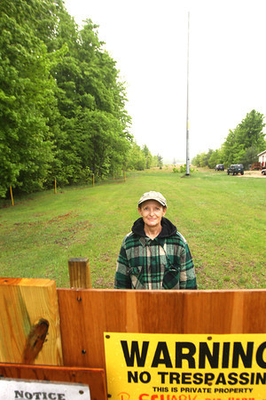 Record-Eagle/Keith King<br /> Pam Schark, of Kingsley, stands Wednesday, May 22, 2013 near signs she posted to try and prevent trees from being cut down near a house she owns in Blair Township.