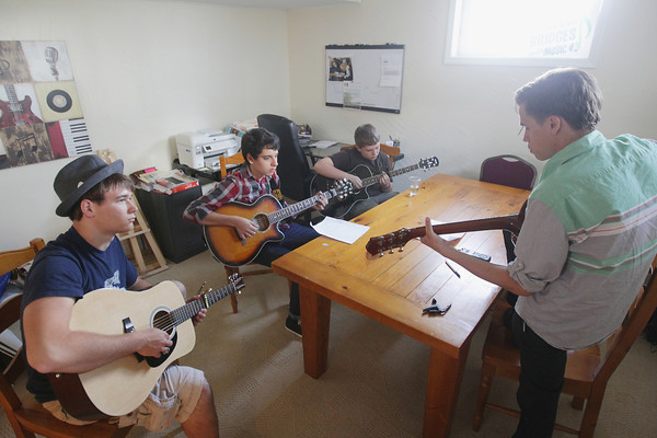 """Record-Eagle/Keith King<br /> Students with Seeking Ecology Education and Design Solutions (SEEDS) John Grocholski, from left, 17, Zak Watson, 15 and Ben Kolk, 15, use their guitars as Graham Parsons, with Earthwork Music, teaches them how to play a song by musician Pat Carroll Tuesday, May 21, 2013 at the Grand Traverse Circuit building on 14th Street in Traverse City. The students, with help from musicians along with Earthwork Music, were learning songs from an album by Pat Carroll titled, """"Glow in the Dark."""" The songs are to be played at a listening party for the album and for Carroll, who is awaiting a lung transplant due to cystic fibrosis."""