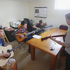 "Record-Eagle/Keith King<br /> Students with Seeking Ecology Education and Design Solutions (SEEDS) John Grocholski, from left, 17, Zak Watson, 15 and Ben Kolk, 15, use their guitars as Graham Parsons, with Earthwork Music, teaches them how to play a song by musician Pat Carroll Tuesday, May 21, 2013 at the Grand Traverse Circuit building on 14th Street in Traverse City. The students, with help from musicians along with Earthwork Music, were learning songs from an album by Pat Carroll titled, ""Glow in the Dark."" The songs are to be played at a listening party for the album and for Carroll, who is awaiting a lung transplant due to cystic fibrosis."