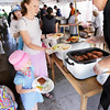 Record-Eagle/Keith King<br /> Sarah Parker, of Traverse City, is served a buffalo burger as her daughters Audrey Parker, 5, and Macy Parker, far left, 2, stand nearby.