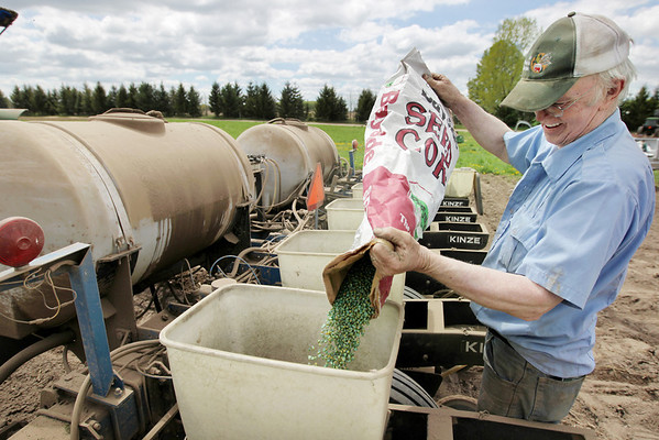 Record-Eagle/Keith King<br /> Richard Dennett dumps corn into a seed box prior to planting it in his field in Buckley.