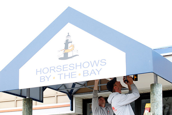 Record-Eagle/Jan-Michael Stump<br /> Paul Wentworth, left, and Doug Saul, of Advanced Awnings Upholstery and Canvas,  install soffit on an awning at a Flintfields Horse Park building.