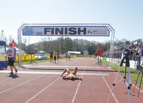Record-Eagle/Keith King<br /> A runner lies down after crossing the finish line during the 32nd annual Bayshore marathon in Traverse City.