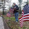 Record-Eagle/Keith King<br /> James Morse Sr., a United States Army veteran, places American flags at veterans' headstones at Greenbriar Cemetery in Almira Township.