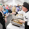 "Record-Eagle/Keith King<br /> Judy Ghastin, of Traverse City, receives beef stroganoff from John O'Rourke, sous chef at Glen Eagle independent living, during the ""Ideas for Life"" Senior Expo at the Grand Traverse County Civic Center."