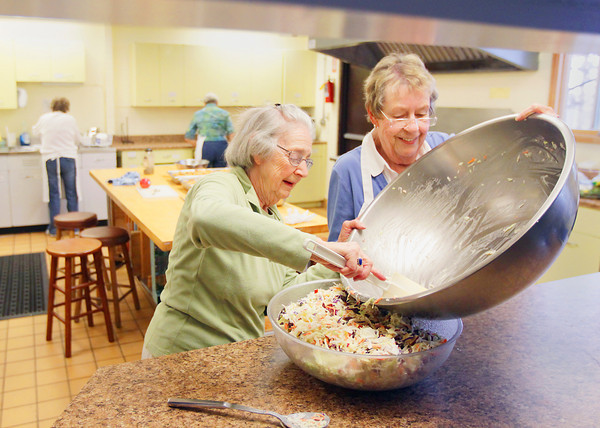 Record-Eagle/Keith King<br /> Maxcella Latimer, left, and Sue Bennett, members of Grace Episcopal Church in Traverse City, along with other members of the church, prepare food Friday, May 17, 2013 for a Grace Episcopal Church community meal.