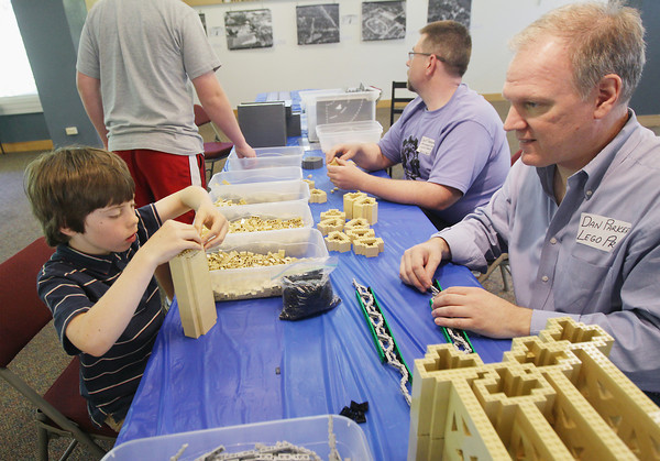"Record-Eagle/Keith King<br /> Boston Price, 8, of Suttons Bay, uses Legos to build a pier for a Lego version of the Mackinac Bridge, as Scot Thompson, back, president of the Michigan Lego Users Group, and Dan Parker, right, a Lego certified professional, build nearby Saturday, May 25, 2013 during the kickoff for ""Lego Carnival: Building Blocks of America""  at the History Center of Traverse City. The Lego event is scheduled to take place through summer. ""That's looking good,"" Parker said as he looks at Price's Lego construction progress."