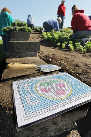 Record-Eagle/Keith King<br /> The Friendly Garden Club and others plant flowers Thursday, June 2, 2011 in the logo garden at the Open Space.