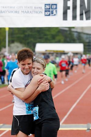 Record-Eagle/Jan-Michael Stump<br /> Runners Sharon Gerrish, of DeWitt, left, and Christy Duffield, of Lansing, celebrate their half-marathon finish in Saturday's 29th annual Bayshore Marathon races.