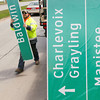 Record-Eagle/Keith King Dustin Jaynes, left, and Brad Peterman, back, foremen with Give 'Em A Brake Safety, prepare a sign for installation along Grandview Parkway. Signs and signposts are being replaced, with some being relocated, along sections of M-72, Grandview Parkway and M-115 as part of a Michigan Department of Transportation project.
