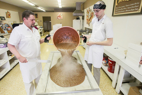 Record-Eagle/Keith King<br /> Dave Murdick, left, and Chay Drexler, pour chocolate from a copper kettle onto a marble table as fudge is made at Doug Murdick's Fudge in downtown Traverse City.