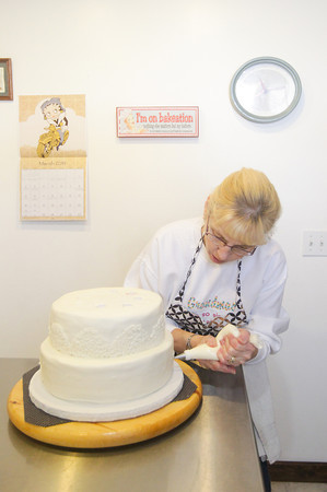 Record-Eagle/Keith King<br /> <br /> Linda Pendock, owner, works on a wedding cake at Kingsley Cakes, in Kingsley.