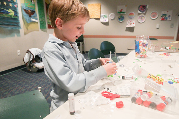 Record-Eagle/Keith King<br /> Owen Meyer, 6, of Traverse City, uses a variety of items such as magnets, stickers and straws to make a model robot at the Traverse Area District Library Woodmere Avenue branch during the Build-A-Bot event. A robotics exhibit, which is to include the Traverse City West Senior High School robotics team, is scheduled for May 31 at the library.