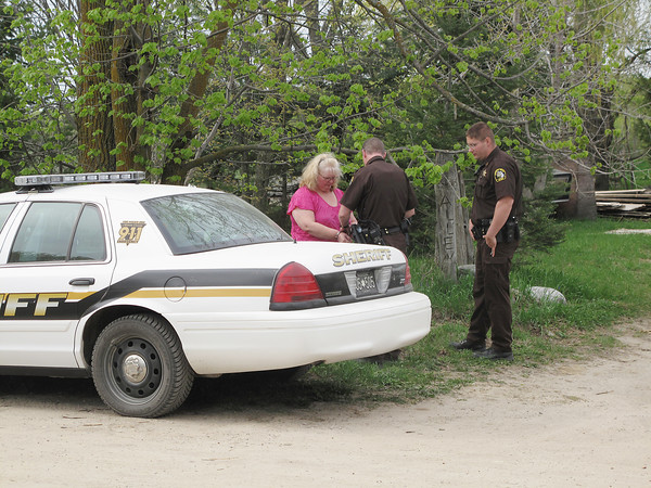 Record-Eagle/Matt Troutman<br /> A woman is arrested Thursday at a Toad Lake Road farm where authorities seized 18 underfed horse