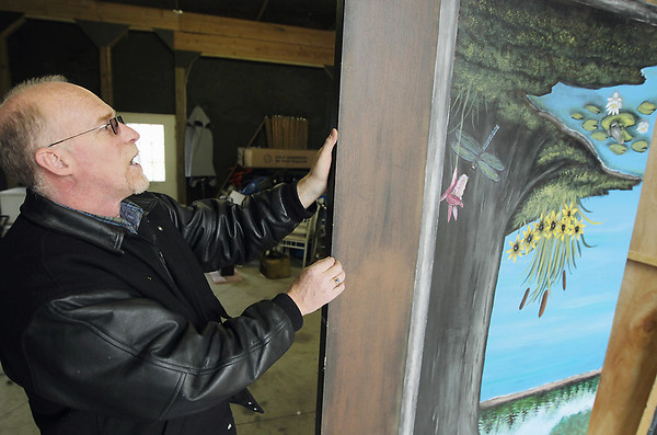 Record-Eagle/Keith King<br /> John Reed shows a panel he made that was painted by Northside Alternative High School students. The panel will be used with others Reed built to form a backdrop for the announcer's stage during the Kalkaska Trout Festival parade.