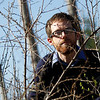 Record-Eagle/Jan-Michael Stump<br /> Matthew Bertrand, invasive species program assitant coordinator at the Grand Traverse Conservation District, crouches among several autumn olive plants, one of the numerous invasive species in the Grand Traverse area.