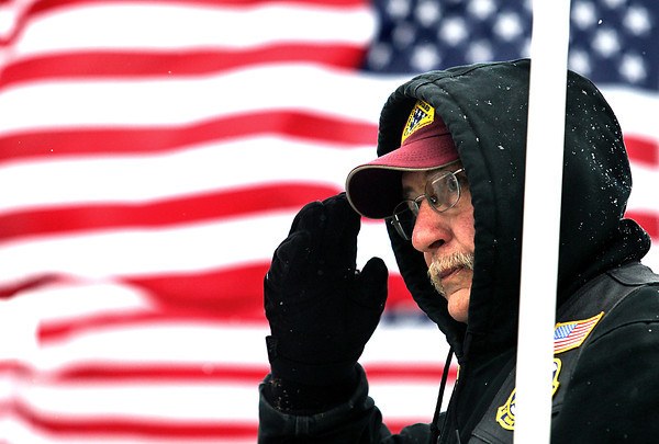 "Record-Eagle/Nathan Payne<br /> Vietnam-era Army veteran Gary Fender salutes a passerby Monday morning while he stands in honor of Veteran's Day along Grandview Parkway with a group celebrating the holiday with the the Grand Traverse Area Veterans Coolition. ""Compared to what these guys have tone through for the country, this is nothing,"" said Tom Whilden from nearby while a group of demonstrators stood in the wind holding flags. ""We have a choice to do this, they didn't."" The pair of men along with about a dozen others stood for about three hours along the roadway showing their respect for veterans."