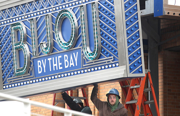 Record-Eagle/Nathan Payne<br /> A&E Signs Installer Chad Wheelock helps guide the Bijou by the Bay marquee down from its mounting position during the installation process Monday afternoon. A handful of workers labored for most of the day alongside a crane to attach the 2,000 pound sign to its mounts in front of the theater facing Grandview Parkway.