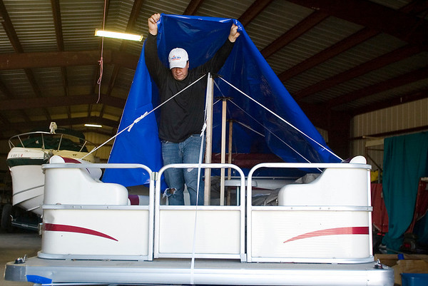 Record-Eagle/Jan-Michael Stump<br /> Jamie Bush of All Seasons Boat and RV Storage in Fife Lake shrink wraps a pontoon boat for the winter.