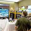 Record-Eagle/Keith King<br /> Jasen Hutchens, far right, of Traverse City, plays a video game near his mother, Barbara Hutchens, of Traverse City, at the Anavon Technologies Group booth Tuesday during the Traverse City Area Chamber of Commerce Business Expo at the Grand Traverse Resort & Spa.