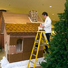 Record-Eagle/Jan-Michael Stump<br /> Grand Traverse Resort Pastry Chef David Sicotte  lays gingerbread tiles on the roof of an approximately 8-foot tall gingerbread house in the resort's lobby on Thursday afternoon. When completed, the house at its 70-foot gingerbread fence will use over 800 pounds of gingerbread and 200 pounds of frosting. The tiles were made a couple weeks ago and allowed to dry out and harden. The frosting, made from powdered sugar and egg whites, dries hard enough to hold up pieces as large as six pounds.