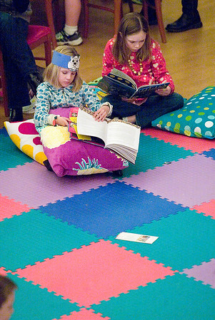 Record-Eagle/Jan-Michael Stump<br /> Jenna Sickle, left, and Sydney Smith, both 8, read in padded area in the middle of the City Opera House floor during Saturday's Children's Book Festival, which featured about 31 exhibitors and live entertainment on stage.