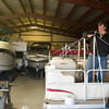Record-Eagle/Jan-Michael Stump<br /> Ed Griffin, top, and Jamie Bush, of All Seasons Boat and RV Storage in Fife Lake, prepare to shrink wrap a pontoon boat for the winter.