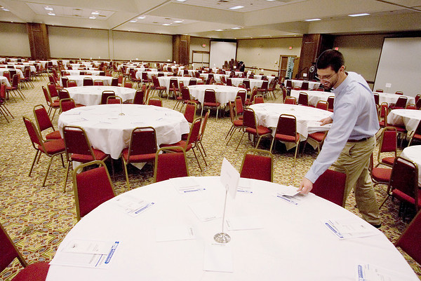 Record-Eagle/Keith King<br /> Nate Jorgensen, communications coordinator with the Traverse City Area Chamber of Commerce, places brochures on tables for the 2011 Economic Outlook Breakfast at the Grand Traverse Resort & Spa. The breakfast takes place before the start of the Chamber Business Expo.