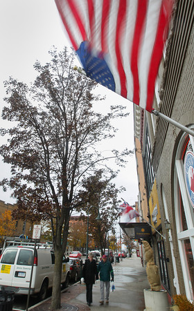 Record-Eagle/Keith King<br /> An American flag flies as Jack and Karen Segal, of Traverse City, walk in windy conditions Monday, November 18, 2013 along Union Street in Traverse City.