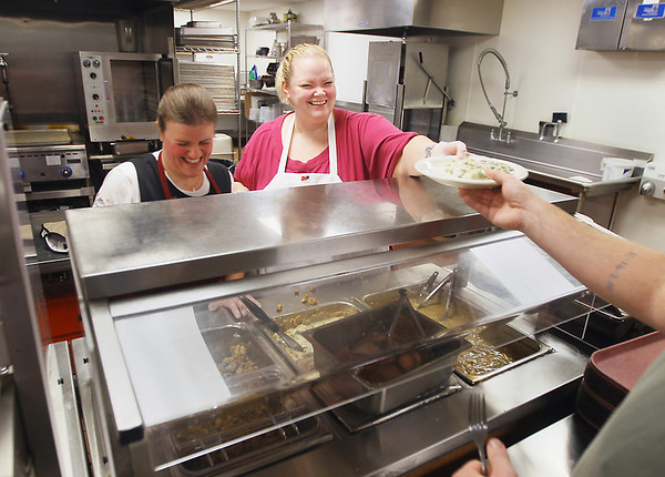 Record-Eagle/Keith King<br /> Julie Olson, right, housing resource specialist, and Folsom Myers, left, volunteer, serve food for a Thanksgiving Day meal Thursday, November 22, 2012 at the Goodwill Inn in Traverse City.