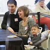 Record-Eagle/Jan-Michael Stump<br /> Kennen Perez, 22 months, sits at a table with his parent's Nick (top) and Nan Perez (middle) as Judge David Stowe finalizes their adoption during Tuesday's Adoption Day proceedings at The Hagerty Center. Twenty-two children were adopted during the event, which was held at the center instead of a courtroom for allow for more space for families.