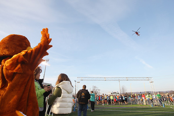 Record-Eagle/Keith King<br /> A United States Coast Guard helicopter flies overhead Thursday, November 22, 2012 after the singing of the National Anthem and prior to the start of the Traverse City Turkey Trot. More than 2,300 people were registered for the event.
