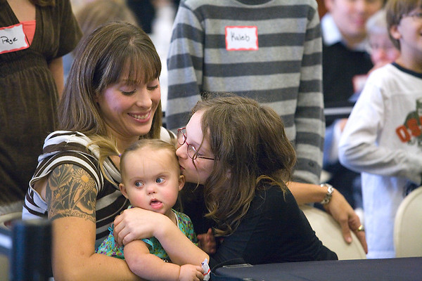 Record-Eagle/Jan-Michael Stump<br /> Ivory Carlson,11, kisses her new sister Payton Carlson, 18 months, in the arms of her mother, Mary Carlson during Adoption Day proceedings Tuesday at the Hagerty Center, where Ivory and her sister Pearl, 10, were adopted by Dan and Mary Carlson of Traverse City.