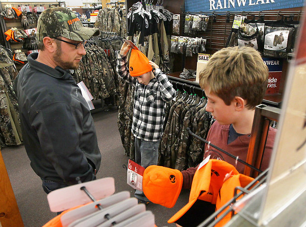 Record-Eagle/Keith King<br /> Corey Hooper, from left, of Traverse City, looks at hats with his sons Clay Hooper, 11, and Cole Hooper, 13, Monday, November 19, 2012 at Gander Mountain in Traverse City.