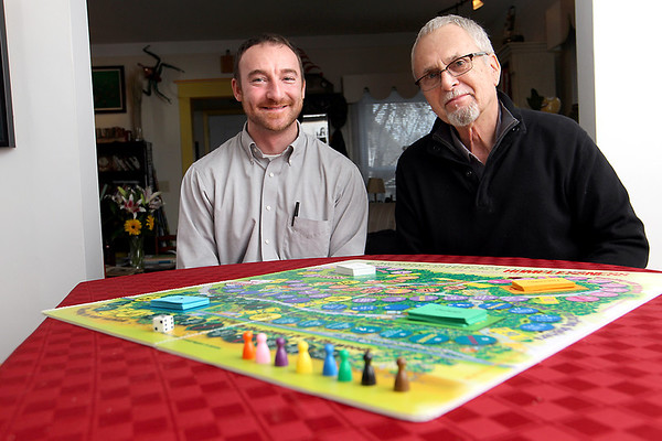 """Record-Eagle/Jan-Michael Stump<br /> Goodwill Industries of Northern Michigan Steet Outreach Coordinator Ryan Hannon, left, and photographer Alan Newton sit with """"Home Sweet Homeless,"""" a board game which allows players to follow in the footsteps of a homeless person as they work towards a home, with setbacks and helping hands to give a great idea of the challenges faced by the homeless."""