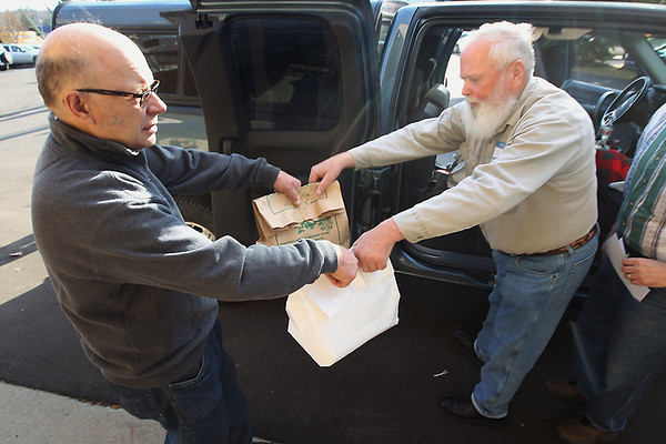 Record-Eagle/Keith King<br /> Volunteer Art Williams, left, of Traverse City, hands bags of food to volunteer Bill Kirkland, of Oxford, at Trinity Lutheran Church to be delivered Thursday, November 22, 2012 as part of the Community Meals Program.