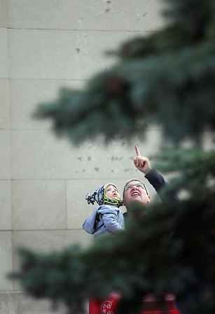 Record-Eagle/Jan-Michael Stump<br /> Bryan Groenevelt of Traverse CIty and his 18 month-old grandson Braden Schulz of Annapolis, Md, watch Traverse City Parks and Recreation workers put up at 40 foot blue spruce Wednesday at the intersection of Front and Cass Streets.